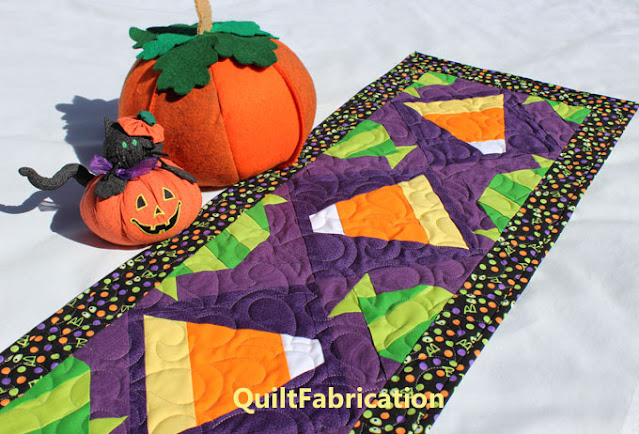 candy corn and green penny candy make a table runner on purple by QuiltFabrication