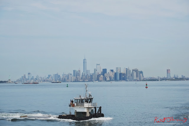 A tug boat Helen Parker, crosses Manhattan Harbor with the Manhattan city skyline and various barges in the distance. Travel photography by Kent Johnson.