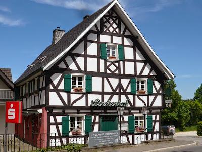 """Ein altes Fachwerkhaus mit grünen Fensterläden. An der Vorderseite prangern die Leuchtbuchstaben """"Lindenhof"""""""