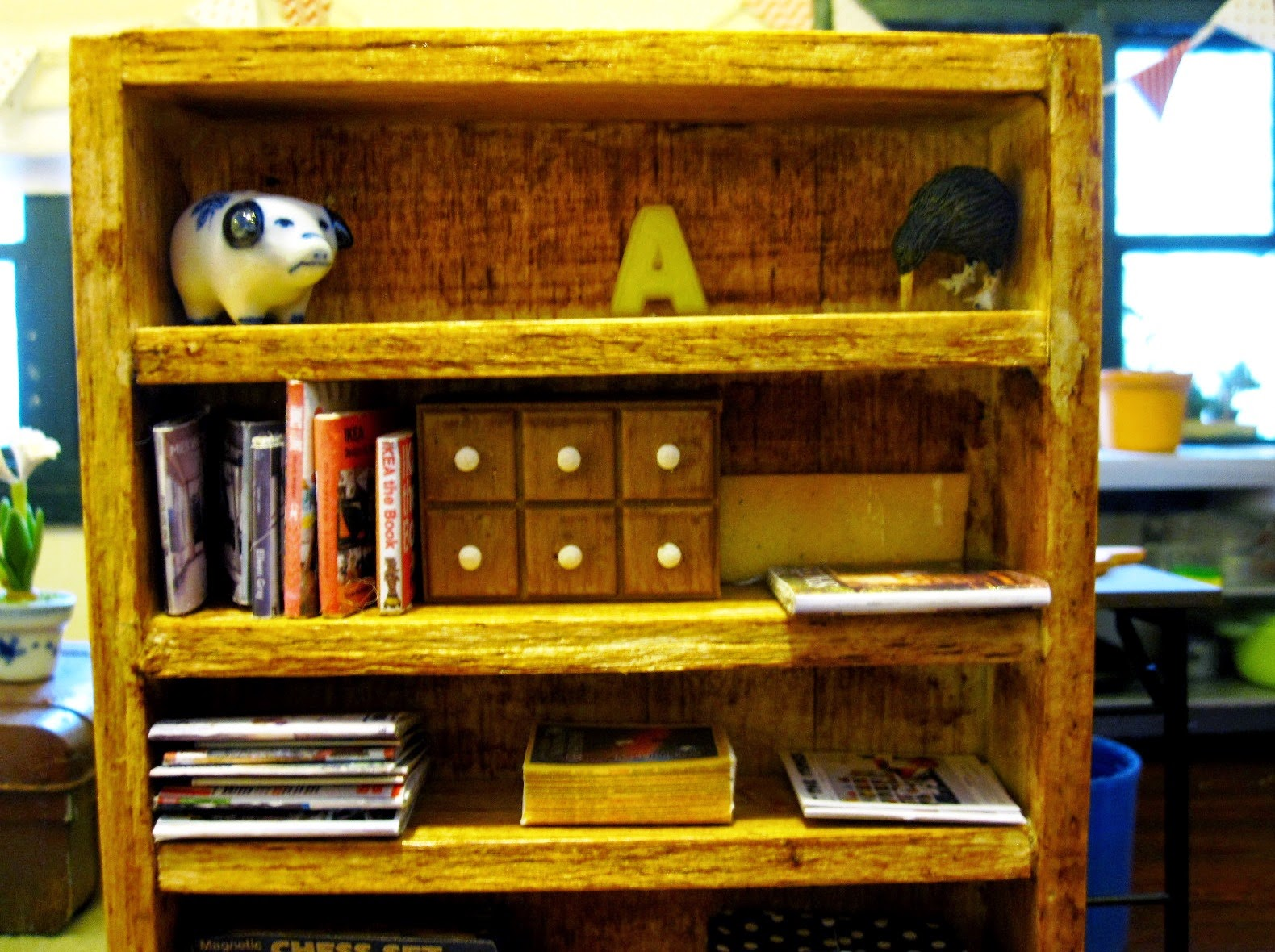 Modern dolls' house miniature bookshelf with books, magazines and a set of spice drawers on display.