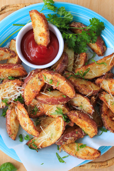 Top viw of parmesan red potato wedges on a blue plate with a side of ketchup.