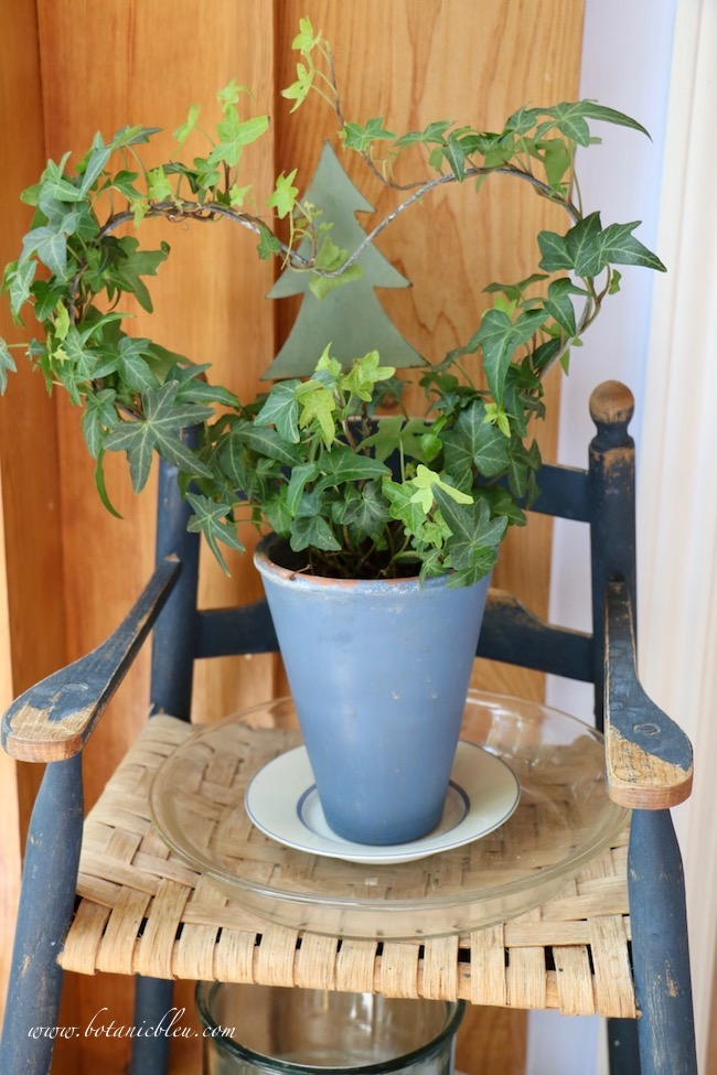 French Country Sunspace includes a vintage worn blue high chair used as a plant stand with an ivy heart topiary