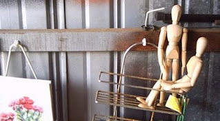 Two wooden artist model figures sitting in a bathroom caddy on my studio wall.