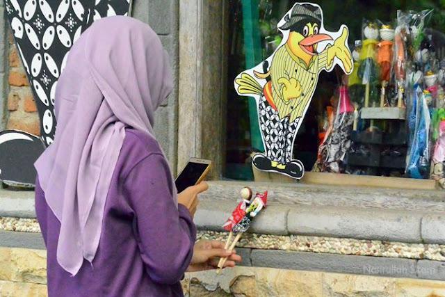Salah satu pengunjung mengabadikan sepasang pensil boneka