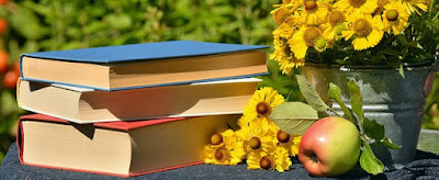 pic of books, table, apple, and flowers
