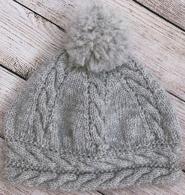 Grey hat with cables knitted with DROPS Karisma using DROPS Extra 0-96 pattern