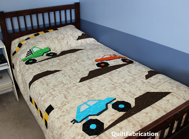 three monster trucks on a twin quilt