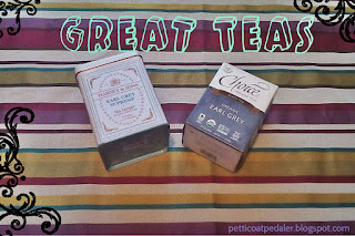 "Striped fabric background or mostly yellows and burgundies.  Two boxes of tea sitting on top of the fabric with the Text, ""Great teas,"" over the image."