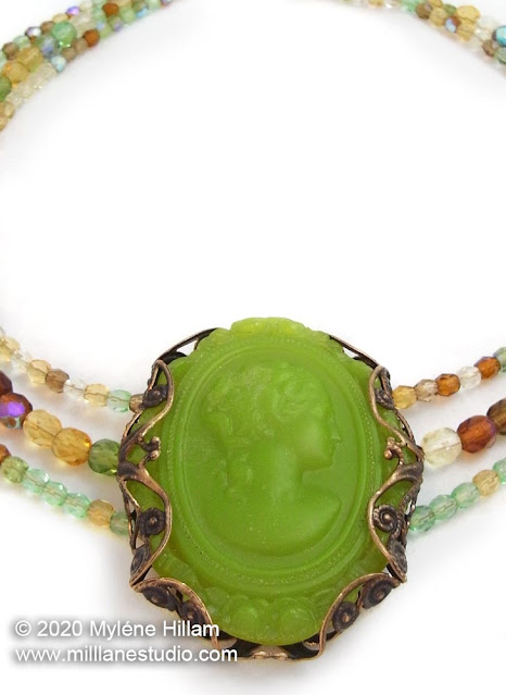 Lime green resin cameo wrapped with a filigree brass stamping, strung with light green, yellow and brown crystals.