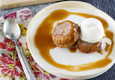two small sweet potato cakes on plate with swirl of sticky caramel sauce and spoon nearby