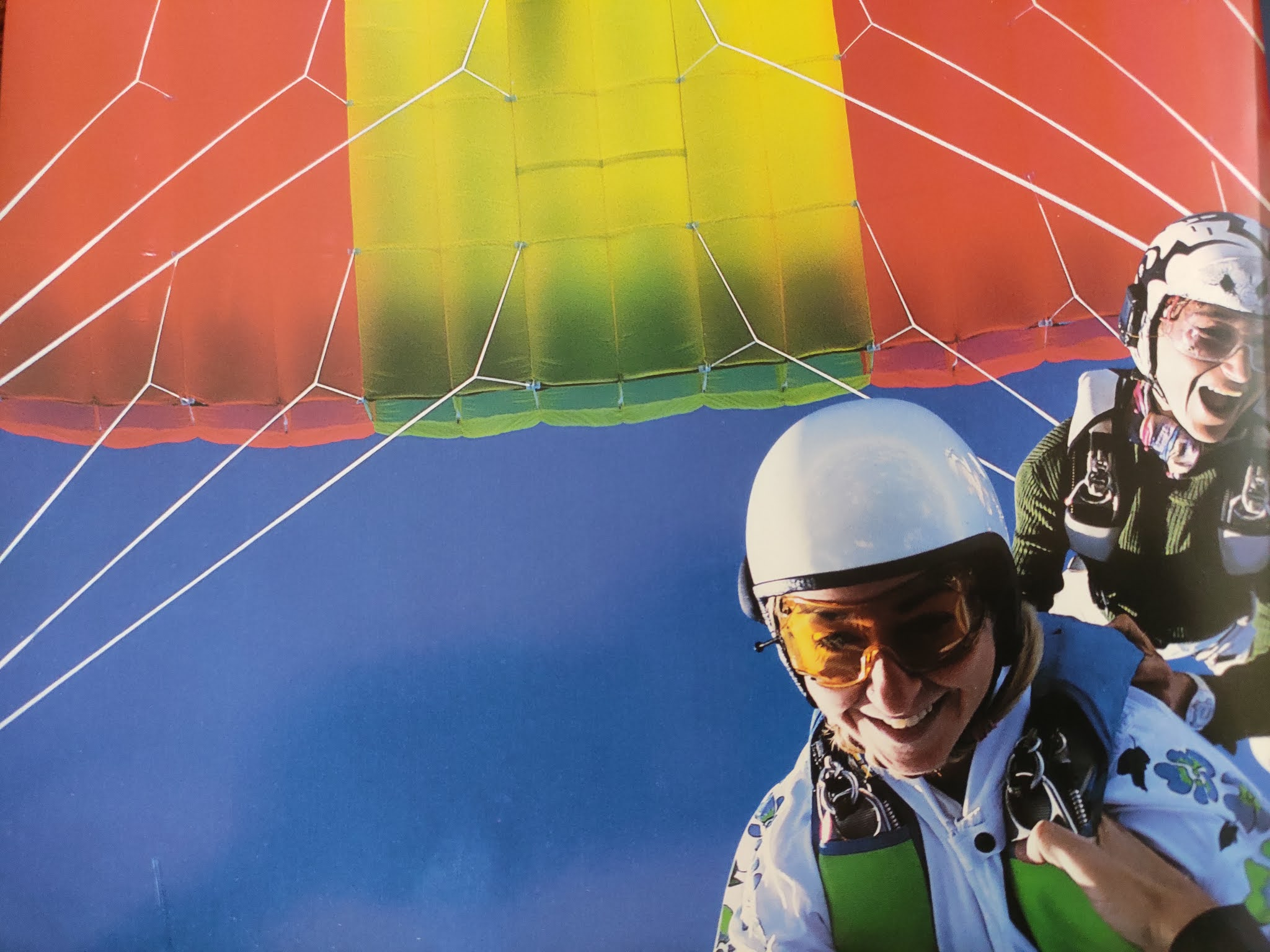 Image contains 2 people paragliding