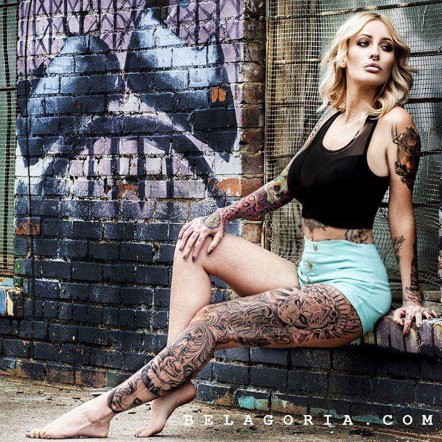 Foto de una modelo en la calle posando, lleva tatuajes en toda la pierna