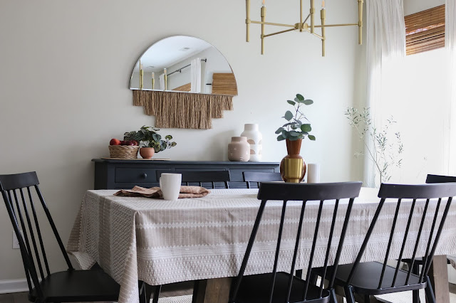 Dining room with black chairs, boho mirror, and boho tablecloth