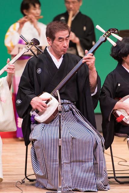 舞台で三味線を弾く男性の写真