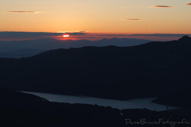 Fotografía de un atardecer con montañas, un lago y el Sol detrás de unas nubes