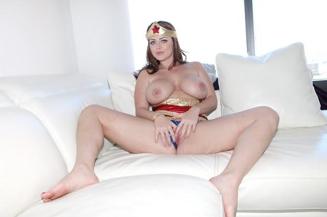 Sophie Dee wonder woman fingering her pussy on sofa