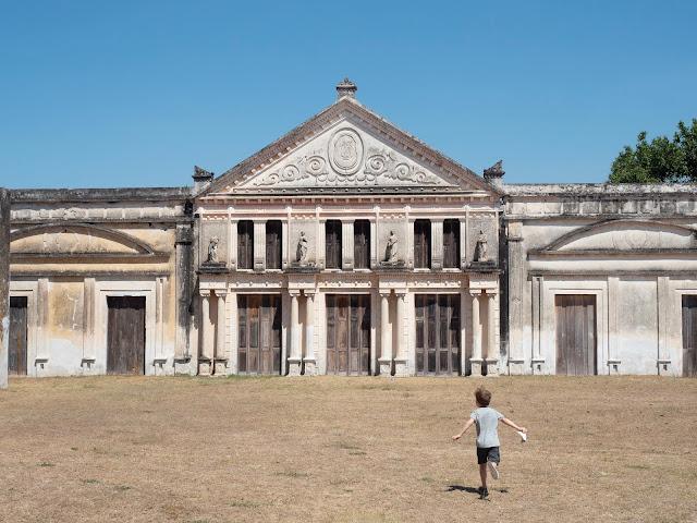 Niño corriendo de espaldas hacia los antiguos almacenes de la hacienda Yaxcopoil