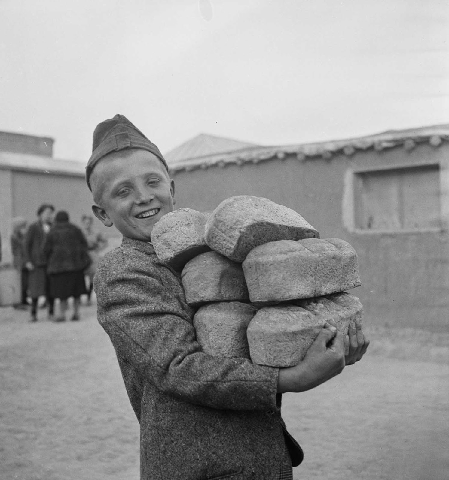 A Polish boy carries loaves of bread provided by the Red Cross.