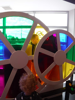 two small blonde children play with two giant color wheels at the Sioux City Art Center's Junior League Hands On Gallery