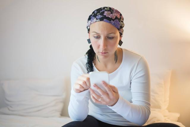 Mujer caucásica con pañuelo de color azul marino en la cabeza sentada en una cama haciendo una búsqueda en el celular de color blanco que tiene en la mano izquierda