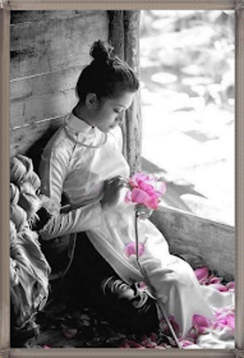 Foto em preto e branco, uma jovem triste sentada com uma rosa despedaçada nas mãos. Apenas a rosa, na tonalidade rosa claro.