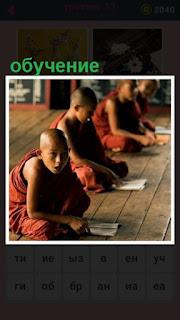 монахи сидят на полу и происходит их обучение