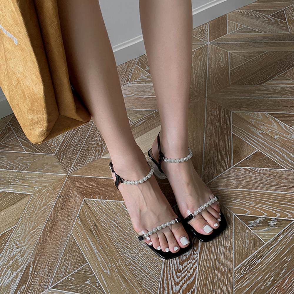 a photo of legs wearing strappy sandals
