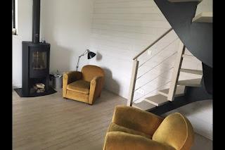 zwei gelbe Sessel, grauer Ofen auf braunem Holzfußboden