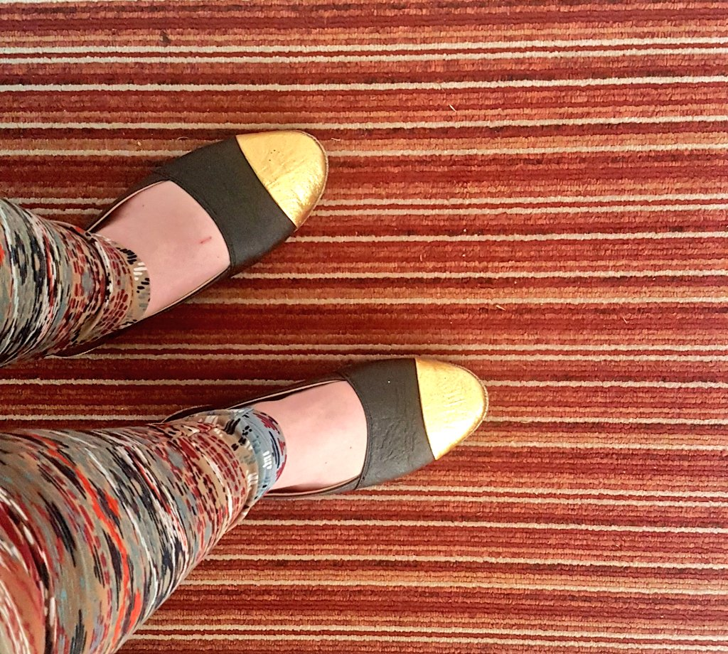 black and gold ballet flats paired with earthy pattern leggings and a striped red and orange carpet