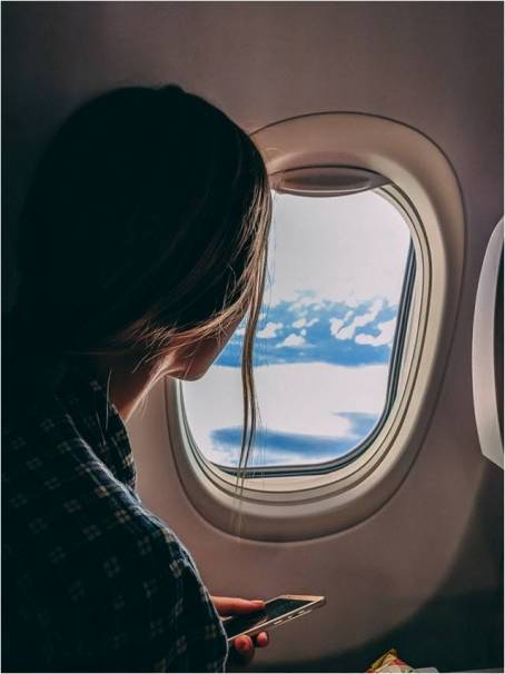 woman in an airplane looking through the window
