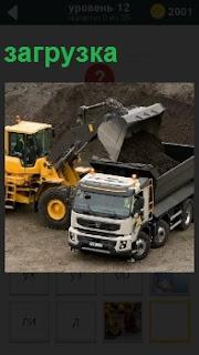 Трактор загружает уголь в машину в карьере в кузов очередную порцию