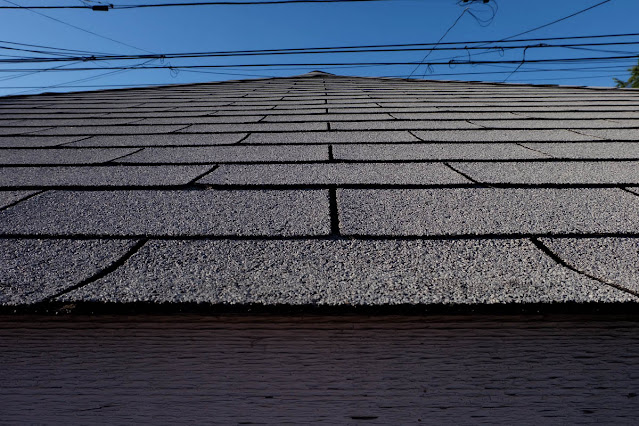 garage roof shingles against blue sky