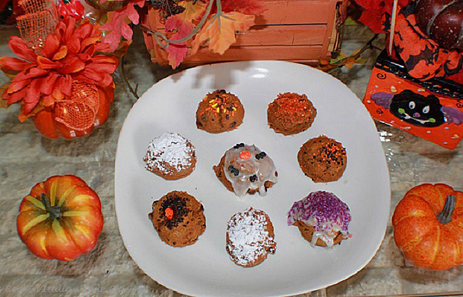 these cookies are all pumpkin spice made with a cake  mix on a white plate and decorated with Halloween colors for fall. is how to make pumpkin spice chocolate chip cookies with a cake mix. Easy spice cake cookies are on a white plate. These are decorated with Halloween black, orange purple sprinkles and colored sugars. There are some pumpkin spiced chocolate chip cookies just dusted with powdered sugar and some frosted with cream cheese frosting.