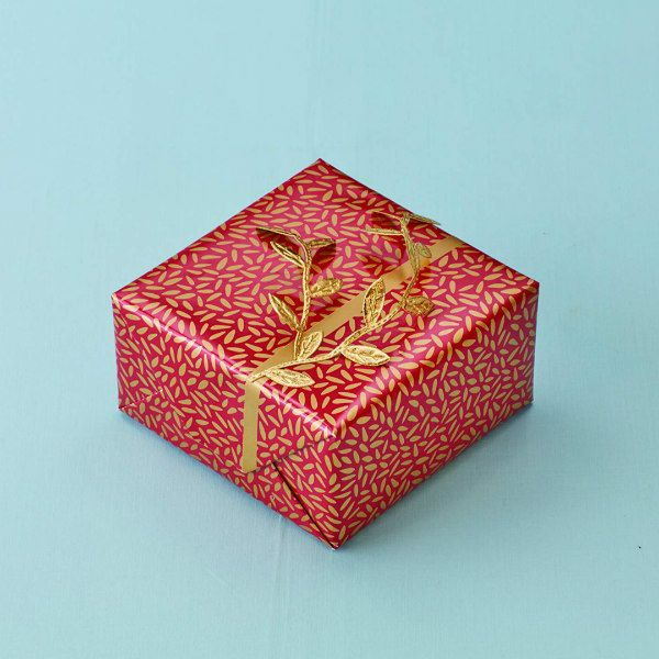 red and metallic gold gift wrapped package with golden leaves ribbon