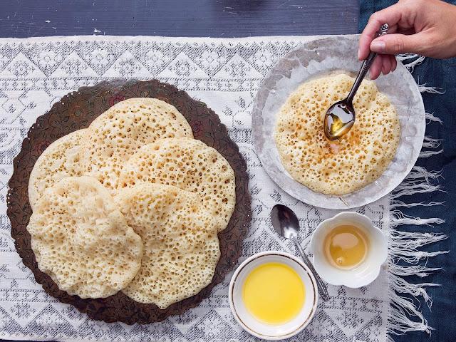 """Baghrir, hay còn gọi là """"bánh nghìn lỗ"""" là một trong những món ngon truyền thống của người Morocco, thường xuất hiện trong những bữa sáng ngày lễ tôn giáo. Những lỗ nhỏ trên mặt bánh là do bột đã được lên men trước khi nấu. Chúng sẽ được phủ với nước sốt bao gồm bơ tan chày và mật ong. Thêm chút hạt nhỏ và hoa quả khô để trang trí thêm cho những chiếc bánh."""