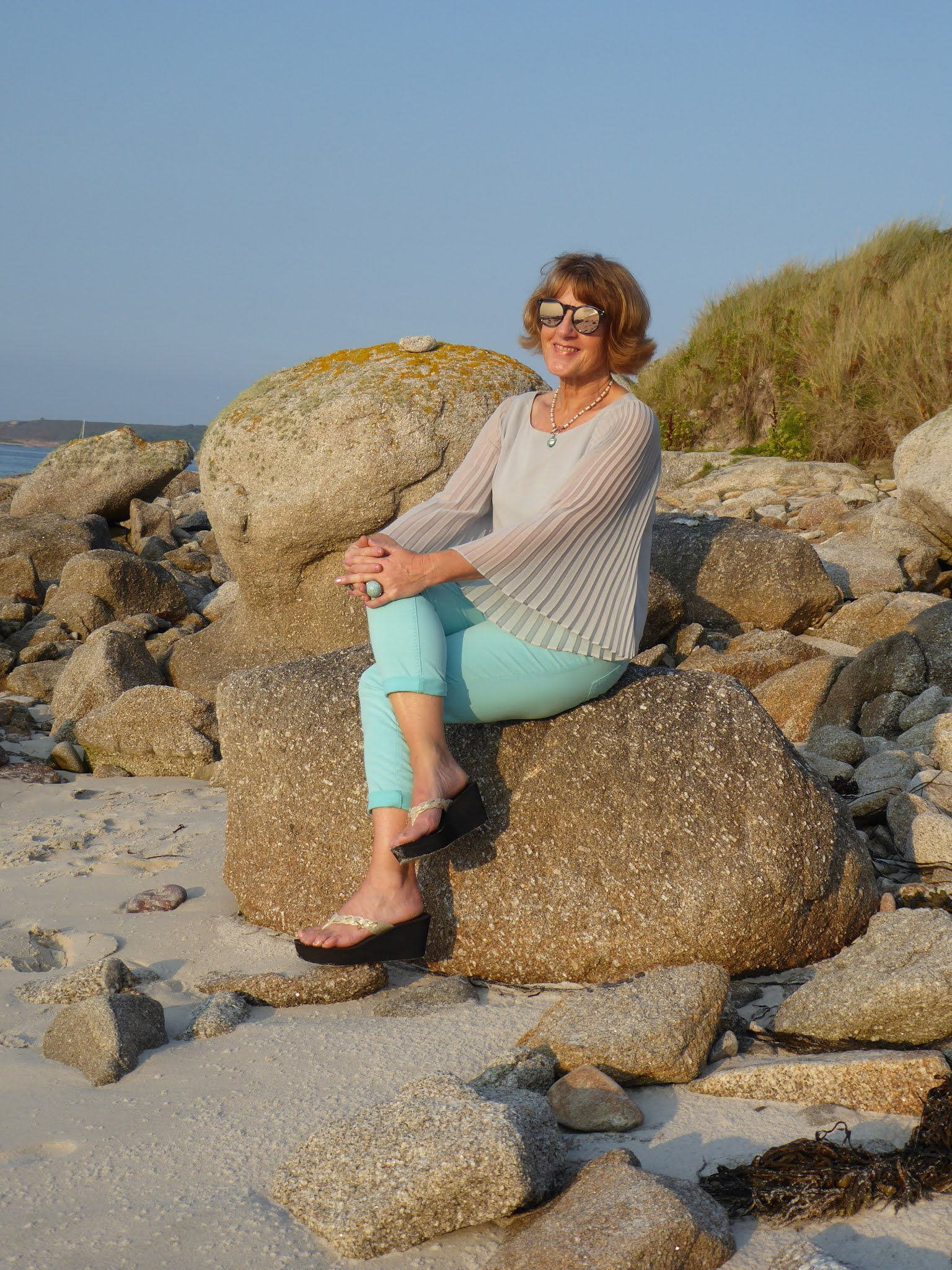Anna from Anna's Island Style in aquamarine trousers and a thrifted top with statement sleeves