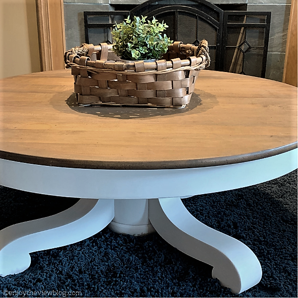 round wood coffee table painted white on the bottom and cappuccino-stained top