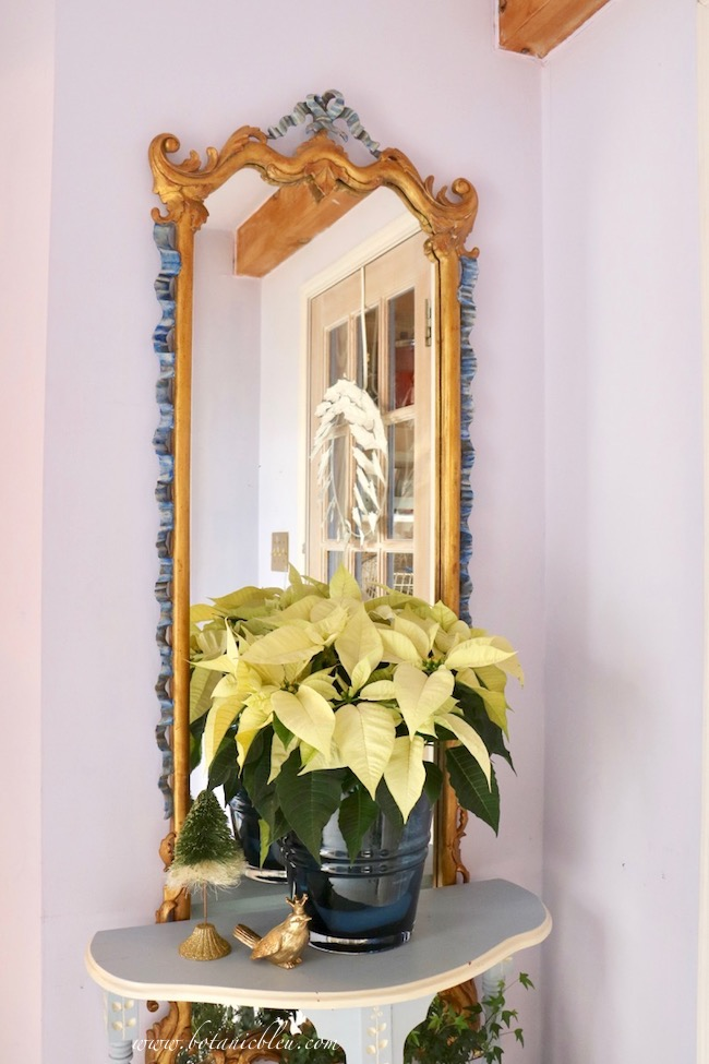 White poinsettia beautiful Christmas entry decor with a French country gold framed mirror