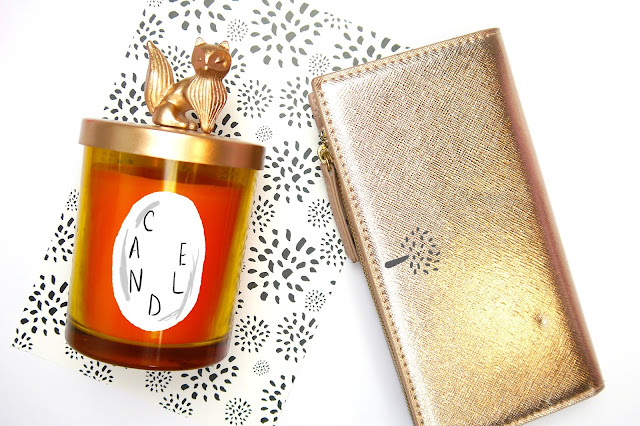 orange candle and rose gold wallet
