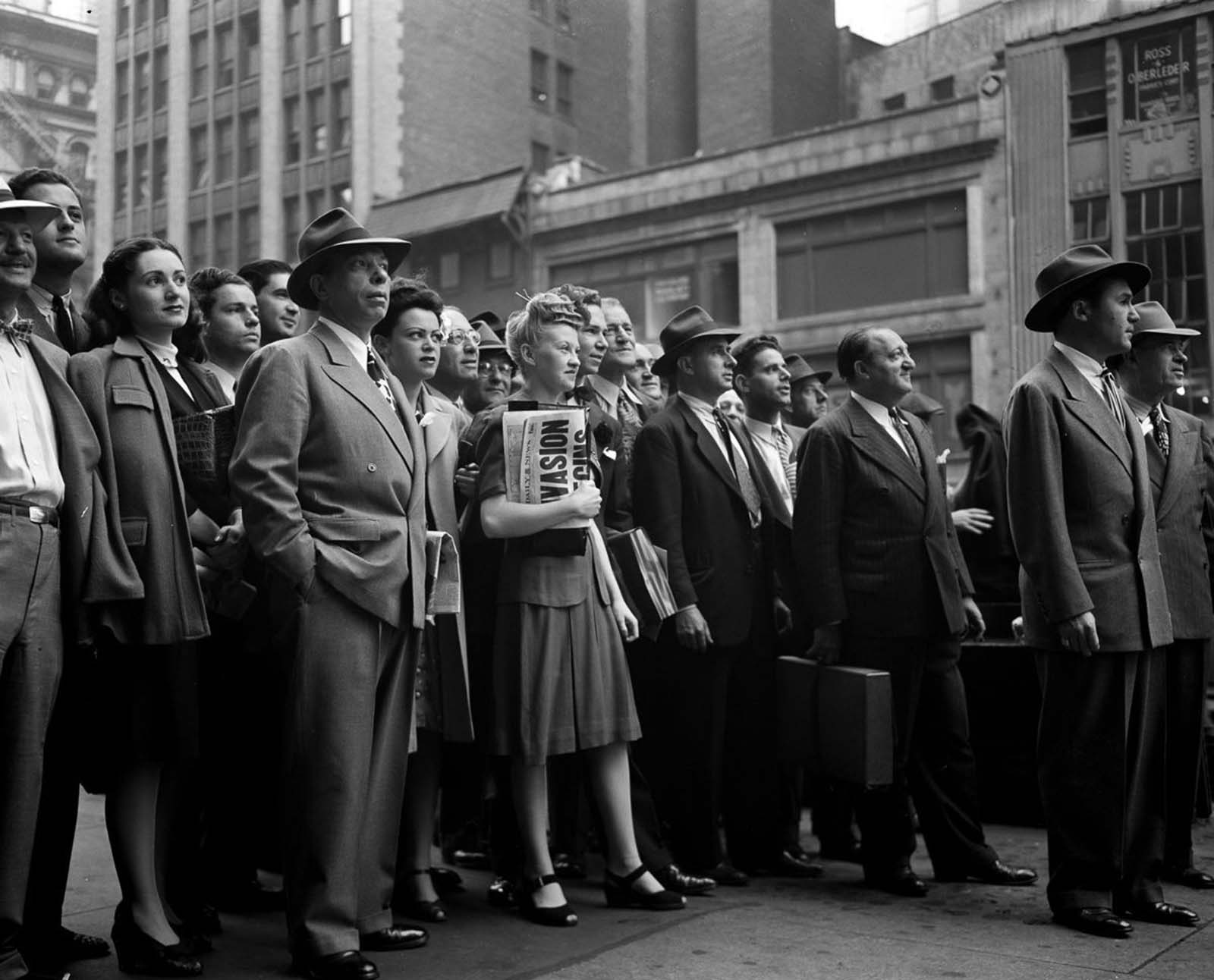 People gather in Times Square to watch the news ticker on the New York Times building.