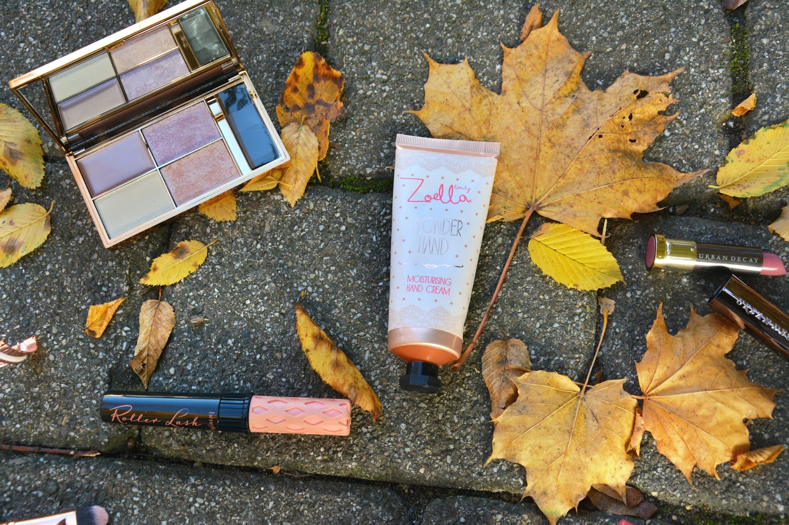 Sleek Solstice Palette; Zoella Handcream; Urban Decay Vice Lipstick; Benefit Rollerlash Mascara; on autumnal background