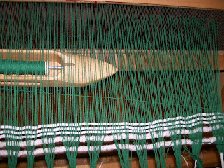 Boat shuttle passing through shed made by raising heddles holding half of the warp threads.