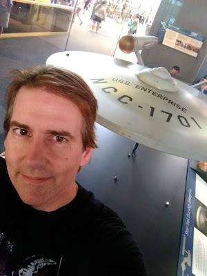Zen Faulkes in front of the USS Enterprise in the Smithsonian Museum