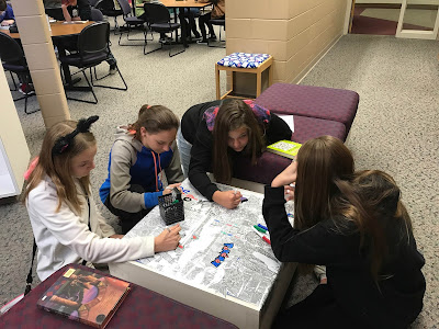 Photo of teenage girls coloring table in library
