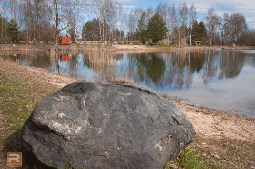 Akmens ar ezeru un pludmali fonā