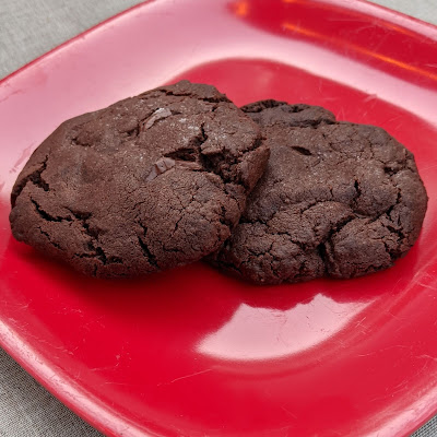 Two dark chocolate cookies together on a red plate.