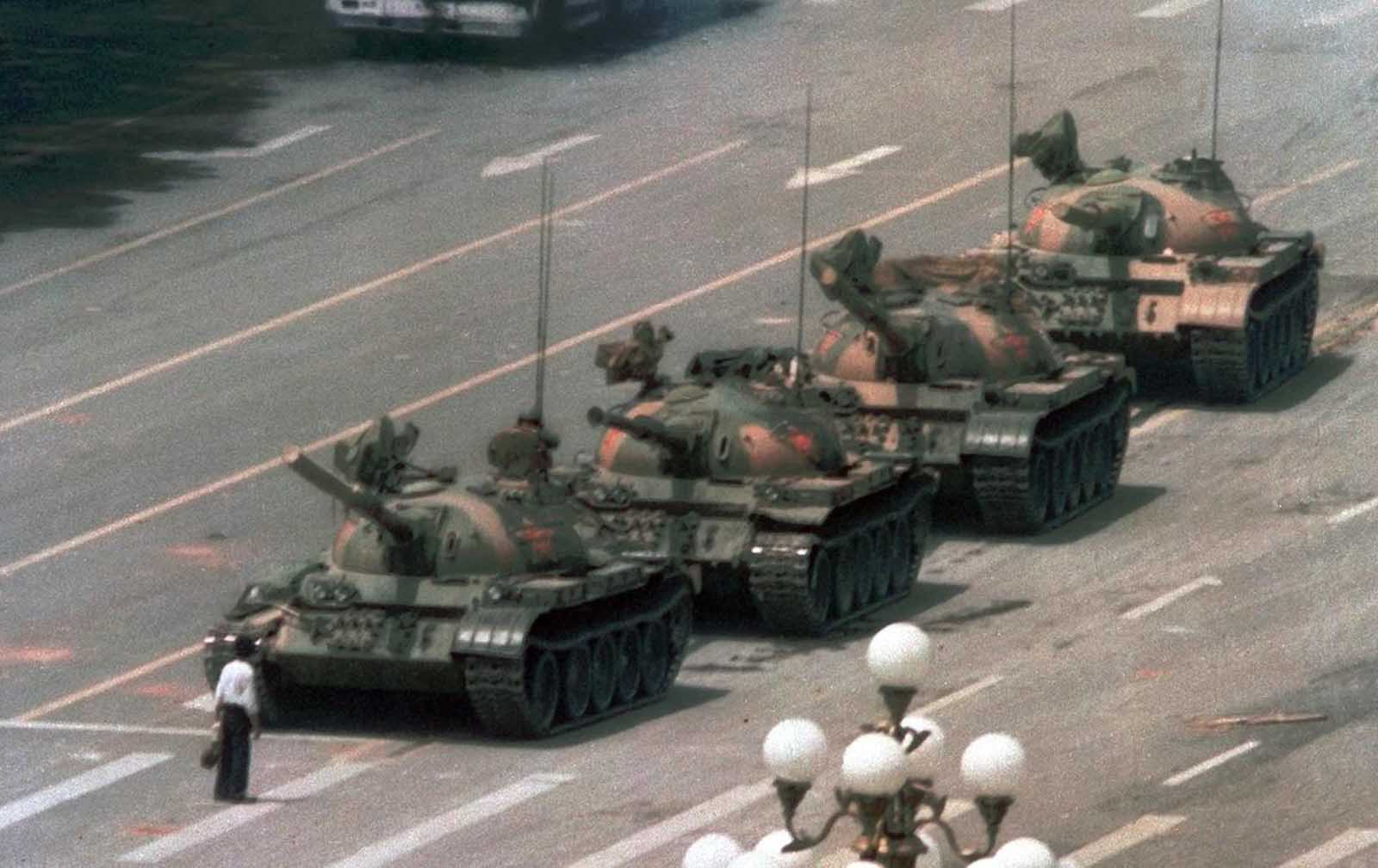 A Chinese man stands alone to block a line of tanks heading east on Beijing's Cangan Boulevard in Tiananmen Square, on on June 5, 1989. The man, calling for an end to violence and bloodshed against pro-democracy demonstrators, was pulled away by bystanders, and the tanks continued on their way.