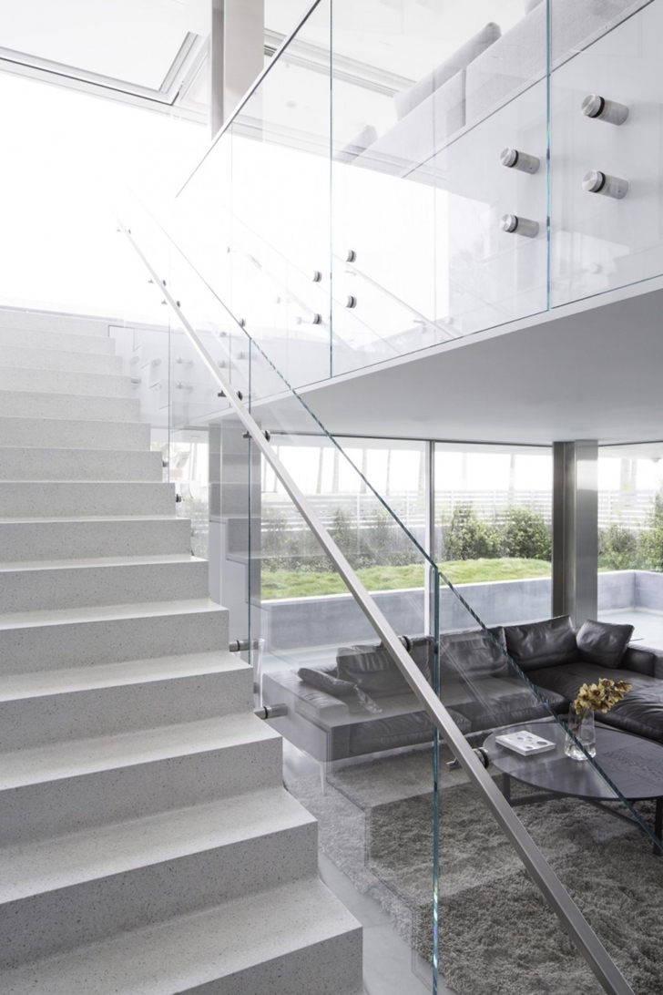 Glass staircase railing in Modern mansion on the beach by Dan Brunn