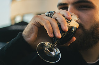 A man drinking wine in a glass.