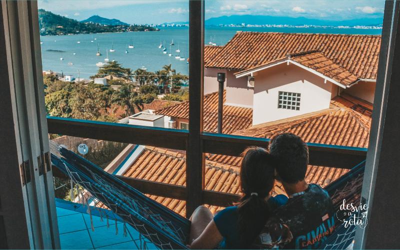 Casal sentado na rede na varando olhando para o mar